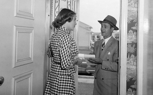 1950s WOMAN ANSWERING DOOR TO MAN IN BUSINESS SUIT SALESMAN WRITING IN NOTE PAD